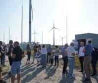 Menschen bei einer Einweihung einer Wärmezentrale unter blauem Himmel und Windenergieanlagen im Hintergrund