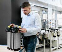 Ein Forscher prüft einen Brennstoffzellenstack im Labor.