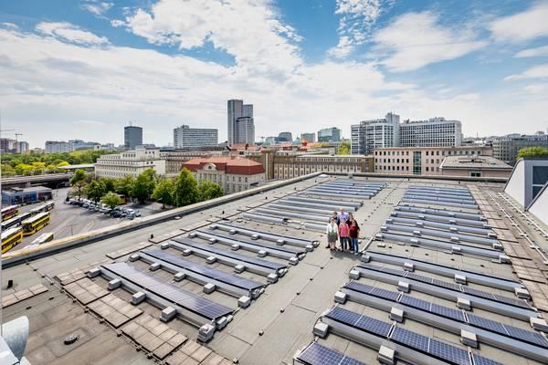 Bürger stehen zwischen Solarmodulen auf einem Flachdach in einer Stadt.