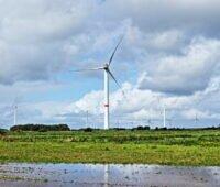 Windpark vor blauem Himmel und Wolken und großen Regenpfützen.