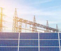 Zu sehen ist ein Übertragungsnetz für Strom mit Photovoltaik-Modulen im Vordergrund. Der Netzentwicklungsplan Strom soll dem Ausbau der Windenergie und des Solarstroms Rechnung tragen.