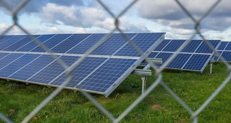 Zu sehen ist eine eingezäunte PV-Großanlage als Symbol für die Verschleppung der Ausbaupfade für Photovoltaik und Windenergie durch die Bundesregierung.
