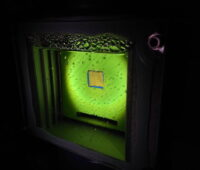 Ein grün schimmernder Wasserbehälter mit einem quadratischen goldenen Katalysator in der Mitte umgeben von Sauerstoffbläschen.