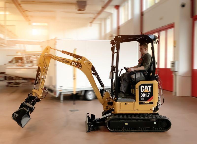 Ein elektrischer Minibagger vob Caterpillar fährt in einer Industriehalle.