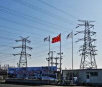 Strommasten und Leitungen vor blauem Himmel. Mittig eine wehende chinesische Fahne.