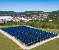Eine solarthermische Kollektoranlage auf grüner Wiese vor einer Fabrik und Hügeln im Hintergrund.