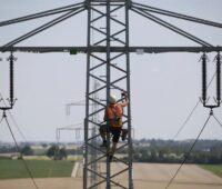 Zu sehen ist die Wartung eines Strommastes. Ist die Krisenfestigkeit in der Zukunft der Stromnetze gesichert?
