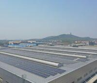 Reihen mit Solarmodulen auf einem großen flachen Industriedach, im Hintergrund Berge und ein Turm.
