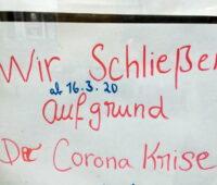Ein handscvhriftliches Schild in einer FEnsterscheibe informiert, dass wegen Corona geschlossen ist.