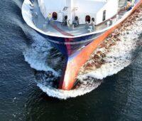 Zu sehen ist der Bug eines Schiffes in voller Fahrt, das zukünftig als batterieelektrische Schifffahrt unterwegs sein könnte.