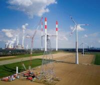 """Aufbau einer Windkraftanlage mit vertikal angeordneten Rotoblättern auf dem Windtestfeld - rechts weitere """"normale"""" Windkraftanlagen und links im Hintergrund ein Kohlekraftwerk"""