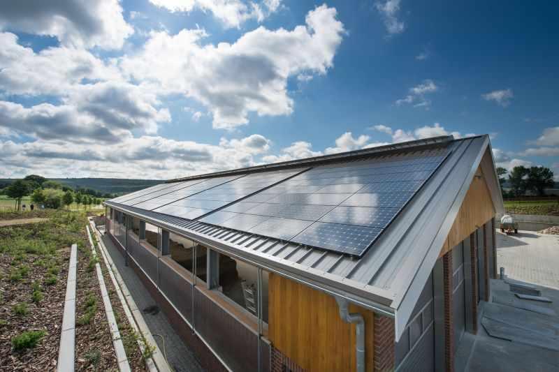Eine Solardachanlage unter blauem Himmel mit Sonne und Wolken.