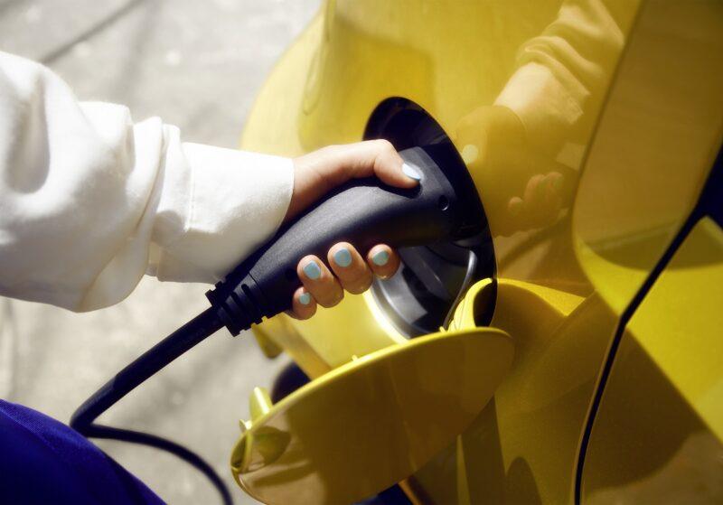 Zu sehen ist eine Frauenhand die das Ladekabel im Stecker eines E-Autos hält. Die Dachgenossenschaft Vianova eG will Mobilität in Gemeinschaft fördern.