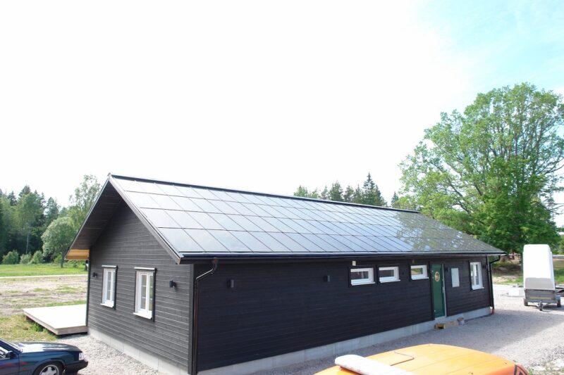 Zu sehen ist ein Holzhaus in Schweden, das dachintegrierte Photovoltaik-Module trägt.