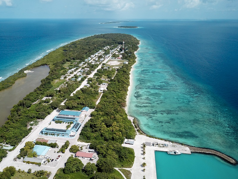 Zu sehen sind vernetzte Photovoltaik-Microgrids auf einer Luftaufnahme einer Insel der Malediven im blauen Ozean.