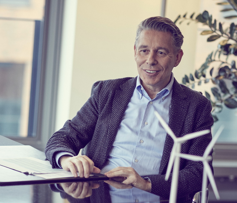 Encavis-Vorstandschef Dierk Paskert lächelnd an seinem Schreibtisch.