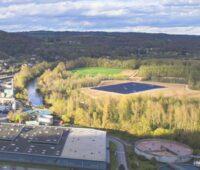 Eine große Solarthermieanlage umgeben von Feldern am französischen Fluss Dordogne. Auf der anderen Seite des Flusses ein Industriebetrieb.
