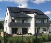 Einfamiliemhaus freistehend mit PV-Anlage auf dem Dach und Garten.