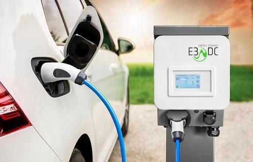 Ein Elektro-Auto steht neben einer Ladestation von E3/DC. Die Fahrzeugbatterie wird gerade geladen.
