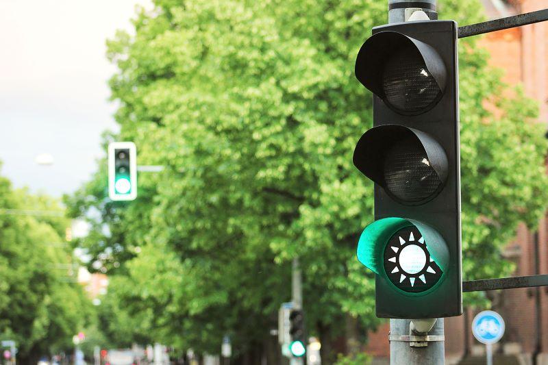 Eine Straßenampel zeigt grün mit dem Symbol einer Sonne.