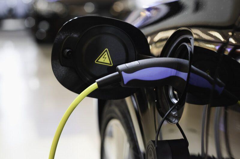 Zu sehen ist das angeschlossene Ladekabel am Anschluss eines E-Autos, für die eigene Ladestation haben Mieter und Eigentürmer von Wohnen ein Recht.