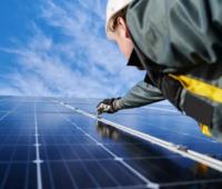 Zu sehen ist ein Monteur, der eine große Photovoltaik-Anlage installiert. Nach den Plänen der EU sollen PV-Anlagen mit mehr als 400 kW Leistung in Zukunft nur dann gebaut werden, wenn der Investor zuvor an einer Photovoltaik-Ausschreibung teilgenommen und einen Zuschlag erhalten hat.