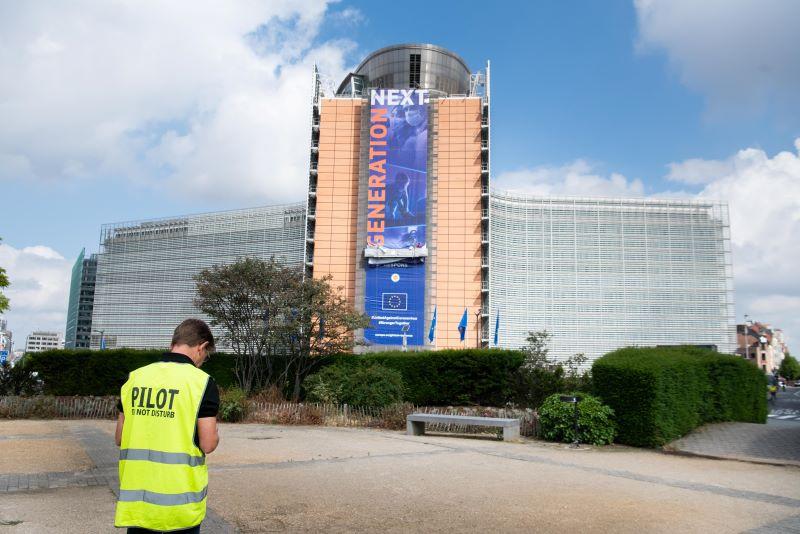Am Sitz der EU-Kommission in Brüssel hängt ein Plakat mit der Aufschrift EU NExt Generation, im Vordergrund in Arbeiter in Sicherweste mit dem Rücken zum Betrachter auf den Boden schauend.