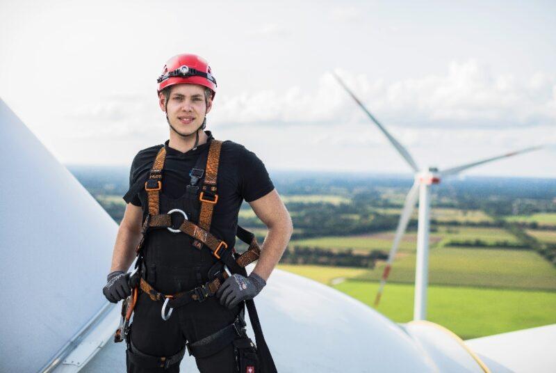 Zu sehen ist eine Techniker auf einer Windenergieranlage. EWE und Enercon legen ihren Bestand an Windparks zusammen.