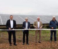 Vier Männer stehen vor einer Photovoltaik-Anlage und durchschneiden ein weißes Band.
