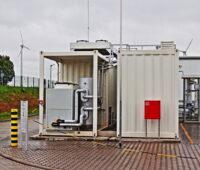 Zu sehen ist ein weißes Metallcontaiber. Darin befindet sich ein Elektrolyseur zur Wasserstoffproduktion der Stadtwerke Mainz und Linde. Im Hintergrund stehen Windkraftanlagen