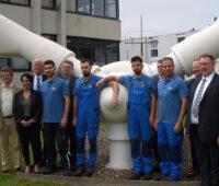 Eine Gruppe von Menschen vor dem Kopf eines im Boden verankerken relativ keinen Rotorkopfes einer Windkraftanlage mit Flügeln