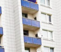Zu sehen ist ein Geschosswohnungsbau mit vielen kleinen Stecker-Photovoltaik-Anlagen an den Balkonen.