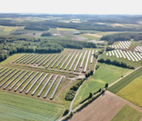 Luftbild einer Photovoltaik-Freiflächen-Anlage aus mehreren Teilfeldern zwischen Wiesen und Wäldern.