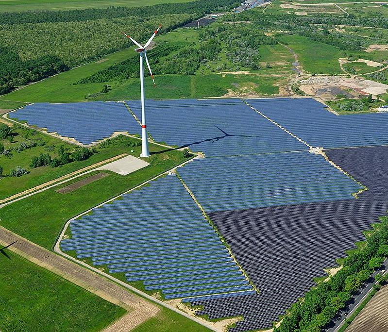 Luftaufnahme eines Freiflächensolarparks mit einer Windkraftanlage