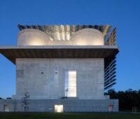 Ein alzter Flakbunker bestrahlt gegen dunklen Himmel, an den Seiten der Fassaden Solarkollektoren.
