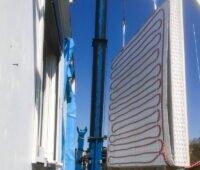 Ein Fassadenelement hängt am Kran zur Montage an der Wand.