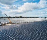 Inmitten einer großen Freiflächen-PV-Anlage arbeitet ein Kran.