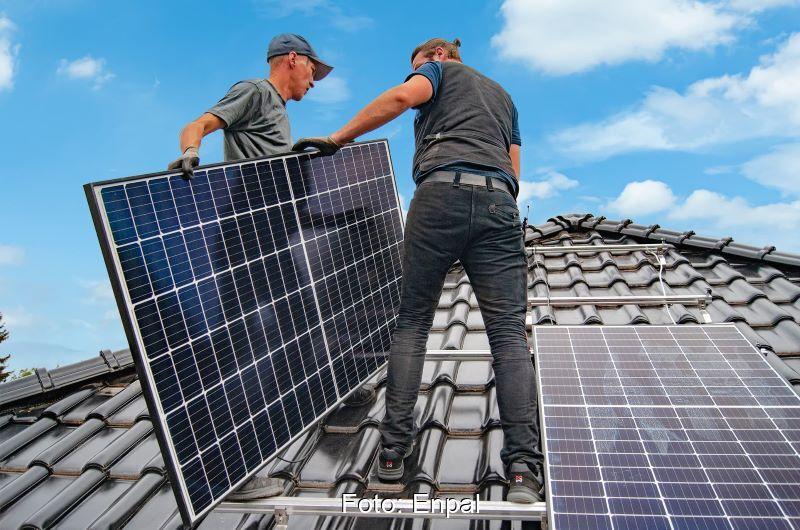 Zwei Installateure mit Solarmodulen auf dem Dach.