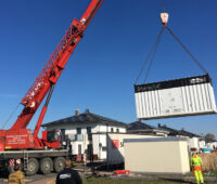 Ein Kran hebt einen Speichercontainer für eine Neubausiedlung.
