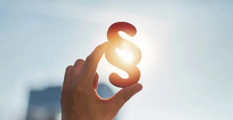 Zu sehen ist ein Paragrafen-Zeichen, das in die Sonne gehalten wird als Symbol für den Entwurf des Steuerbare-Verbrauchseinrichtungen-Gesetz.