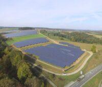 Aus der Vogelperspektive ist ein großer Solarpark zu sehen. Am Rand verläuft eine Autobahn.