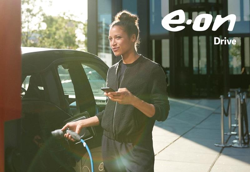 Zu sehen ist eine Frau beim Laden eines E-Autos. Das Eon Analyse-Tool OMNe kann nun Photovoltaik für betriebliche E-Auto-Ladestationen berechnen.