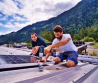 Montage von Solarmodulen auf Metalldächern vor Schweizer Bergpanorama.