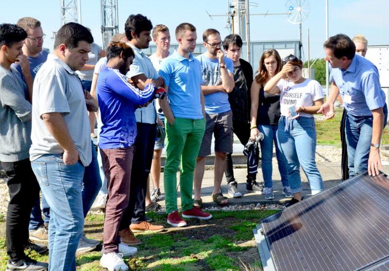 Studenten hören im Freien einem Lehrer zu, der an einem Photovoltaikmodul steht.