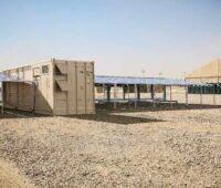 Ein Container eingerahmt von Photovoltaikmodulen in der Wüste.