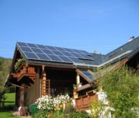 Auf einem Bauernhaus ist eine PV-Anlage installiert. Im Vordergrund sind Blumen gepflanzt.