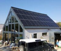 Haus mit Spitzdach, das eine PV-Anlage enthält, die auch Wärme produziert.