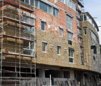 Die Fassade eines mehrstöckigen Gebäudes wird im Zuge einer Sanierung gedämmt.
