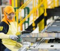 Produktions-Mitarbeiterin mit orangem Kopftuch kontrolliert Photovoltaikmodule in der First-Solar-Fabrik in Malaysia