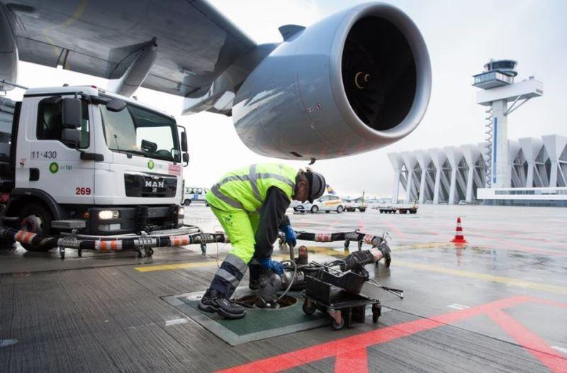 Ein Arbeiter hantiert mit einem tankstutzen unter der Turbine eines Flugzeugs.